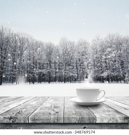 Hot drink in the cup on wooden table over winter snow covered forest. Beauty nature background - stock photo
