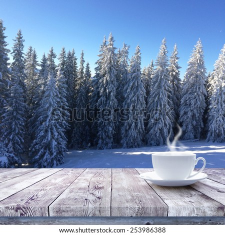Hot drink on wood table over winter forest nature background - stock photo