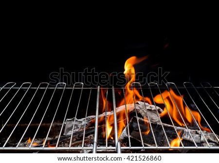 Hot Empty Charcoal BBQ Grill With Bright Flames On The Black Background. Cookout Concept. - stock photo