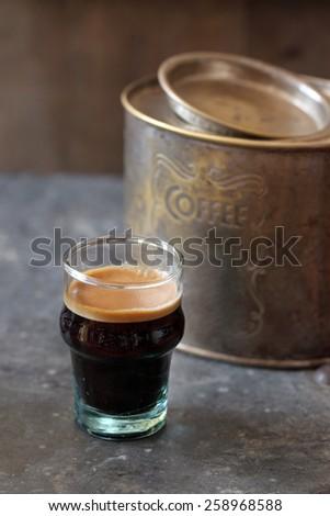 hot espresso coffee glass cup with rusty coffee tin box - stock photo
