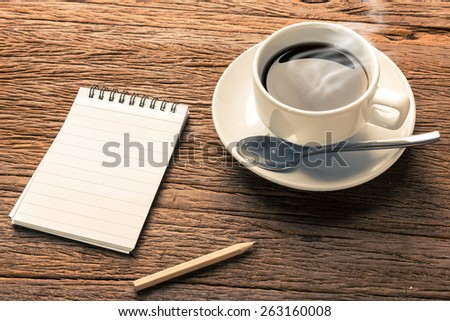 Hot espresso coffee on table with note book and pencil. Concept for business message. - stock photo