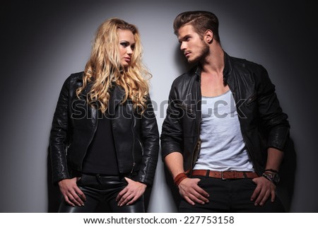 Hot fashion couple leaning on a grey wall while looking at each other, both holding their thumbs in the pockts. - stock photo