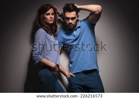 Hot fashion couple posing together, both fix their hair while looking at the camera.