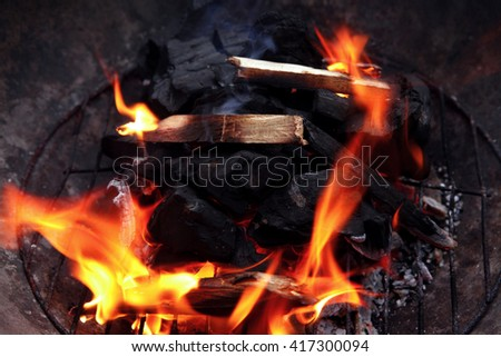hot fire black wood charcoal in big round bbq - stock photo
