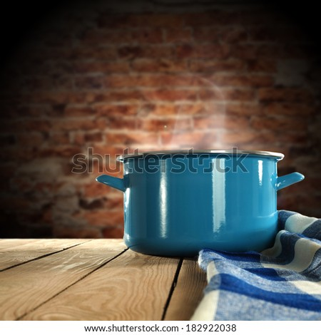 hot food in metal pot on table with napkin
