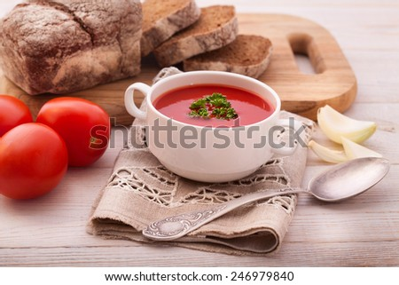 hot fresh diet tomato red soup with  parsley  on wood table - stock photo