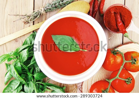 hot fresh diet tomato soup with basil thyme and dry pepper in big bowl on wood table - stock photo
