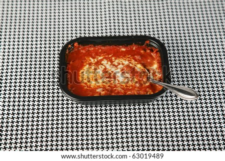Hot fresh from the Microwave oven a Lasagna tv dinner sits on a black and white background waiting to be eaten by a hungry person about to watch their favorite tv program - stock photo