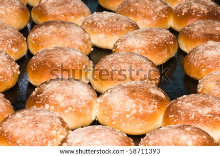 Hot fresh rolls are taken out from oven