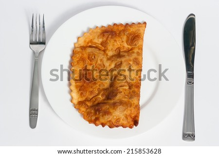 hot fried cheburek  on a white plate on a white background, with fork and knife,  meat pie - traditional snack originally from Asia. - stock photo