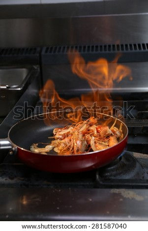 hot fried shrimps on pan with flame in kitchen - stock photo