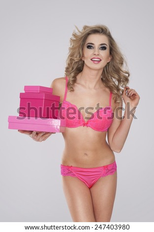 Hot girl in pink lingerie holding stack of gifts - stock photo