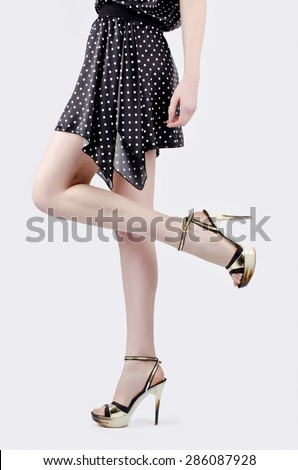 Hot girl with mini skirt and sexy long legs in high heels. A peek of sexiness.  - stock photo