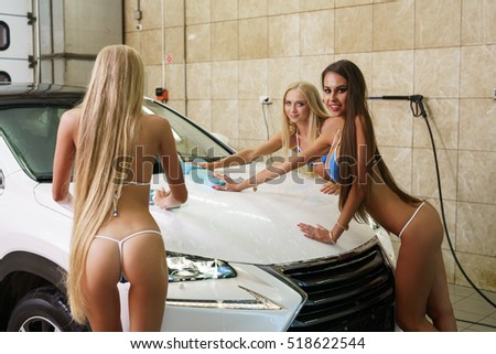 Hot girls pose at camera while washing car's hood