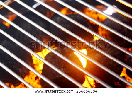 Hot glowing charcoal in a barbecue ready for cooking the meat and veggies over the wire grill, full frame background - stock photo