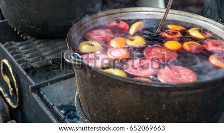 Hot gluhwein or mulled wine in a cauldron at fair, local treat, warm and spicy