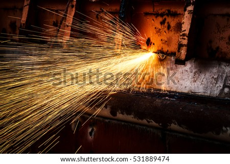 hot golden sparks flying from worker to cutting steel in a construction site with oxygen-propane cutting