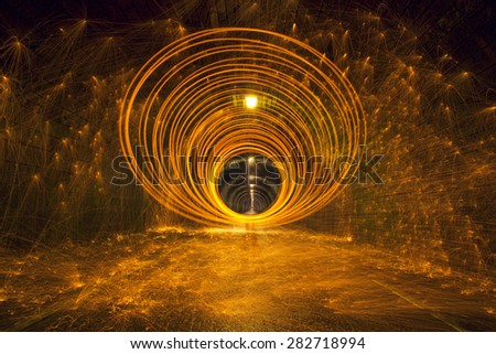 Hot golden sparks Flying off spinning Burning Steel Wool in undergound tunnel - stock photo
