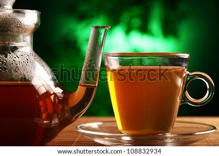 Hot green tea in glass teapot and cup on the table - stock photo