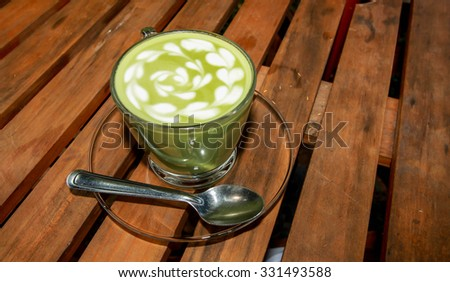 Hot green tea in grass cup on the wood table