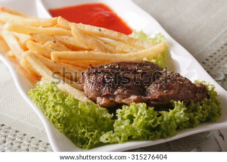 Hot grilled beefsteak with french fries and sauce on a plate macro. horizontal