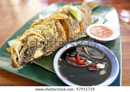 Hot grilled fish, blend in spices and layered in banana leaf (shallow depth of field) - stock photo