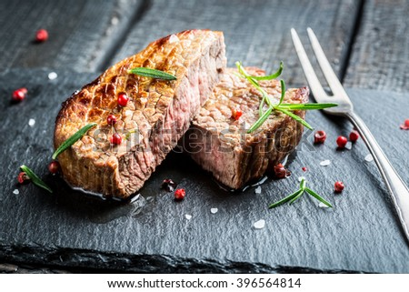 Hot grilled meat with fresh rosemary on plate - stock photo