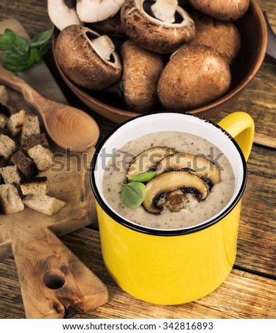 Hot homemade mushroom soup with fried mushrooms  in yellow mug on wooden rustic table and bowl with fresh raw mushrooms, toned
