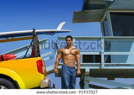 Hot hunky lifeguard on beach with truck and lifeguard stand - stock photo