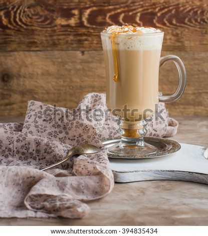 Hot irish cream coffee with whipped cream and caramel topping standing on small saucer on old white cutting board. Textile napkin to the left. Wooden and light beige concrete backgrounds. - stock photo