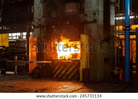 Hot iron in smelter held by a worker - stock photo