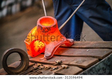 Hot iron in smeltery held by a worker - stock photo