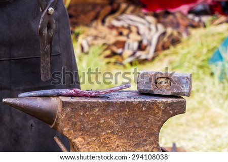 Hot iron on anvil for forging in outdoor workshop - stock photo