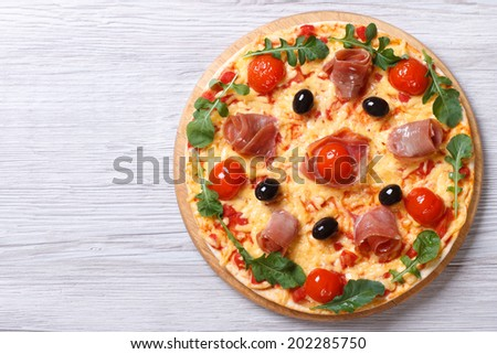 Hot Italian pizza with prosciutto and arugula on the wooden background. top view horizontal - stock photo