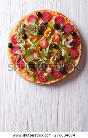 Hot Italian pizza with rocket salad and salami, vertical view from above  - stock photo