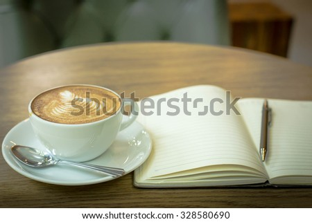 Hot latte art coffee cup on wooden table and note book, vintage and retro style
