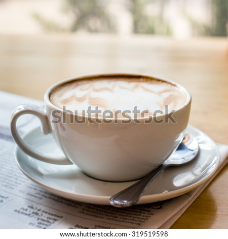 Hot latte art coffee cup with newspaper on wooden table, vintage and retro style - stock photo