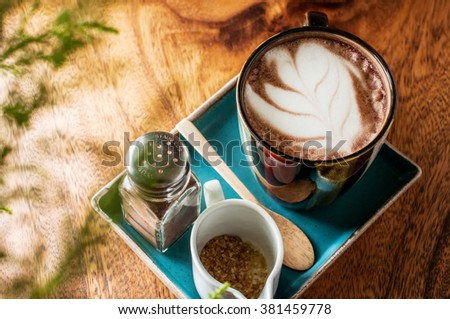 hot latte art coffee on wooden table, vintage and retro style. - stock photo