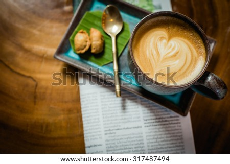hot latte art coffee with newspaper on wooden table, vintage and retro style. - stock photo