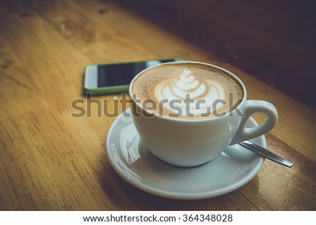 Hot latte art coffee with smart phone on wooden table.