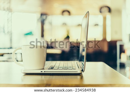 Hot latte coffee cup and laptob in coffee shop - vintage effect style pictures - stock photo