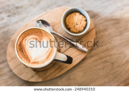 Hot Latte Coffee heart art and cookie on the wooden table - stock photo