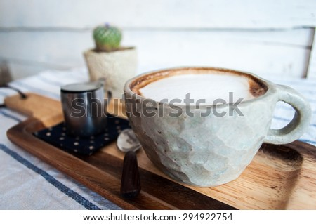 Hot Latte Coffee on wooden saucer with cactus background - stock photo
