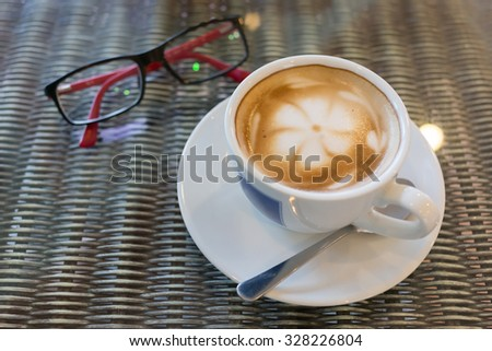 hot latte coffee, white cup on table, flower latte art coffee in cafe coffee shop - stock photo