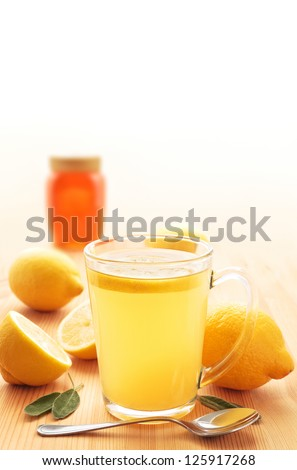 Hot lemon drink in a glass mug on wood with honey, lemons and sage leaves - stock photo