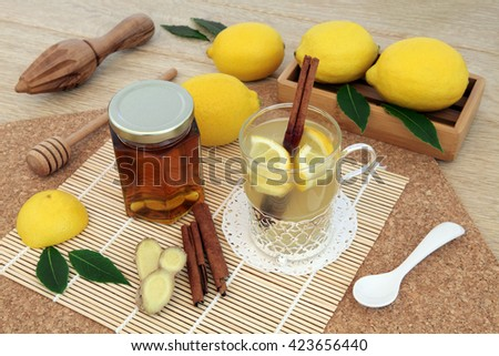 Hot lemon, honey and ginger drink for cold remedy in a glass tea cup with cinnamon stick spice and fresh fruit   on bamboo over cork and oak background. - stock photo