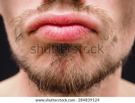 Hot male lips with untrimmed beard at closeup - stock photo