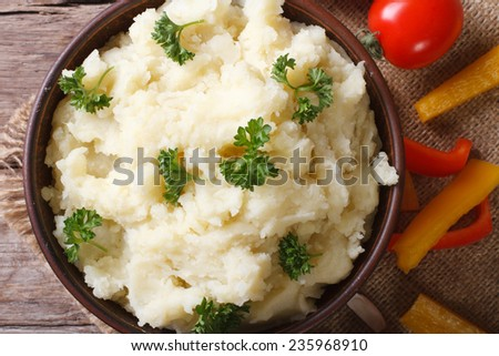 Hot mashed potatoes with parsley in a bowl close up and vegetables on the table. Horizontal top view  - stock photo