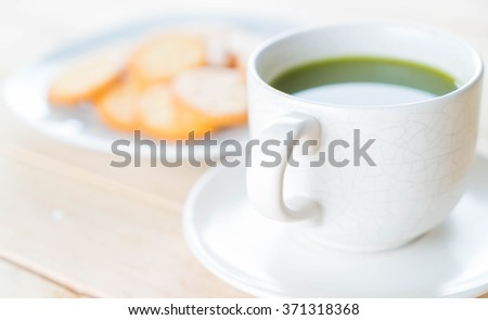 hot matcha on wood background - soft focus with vintage film filter