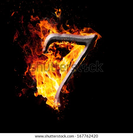Hot metal burning numbers on black background - number seven - stock photo